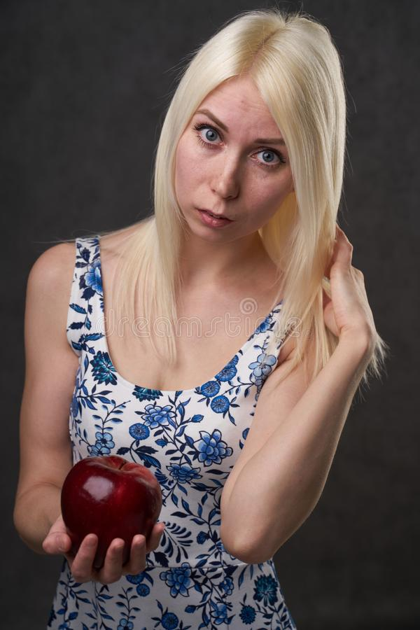 Beautiful girl in a fashionable dress with apple. Portrait composition stock photo