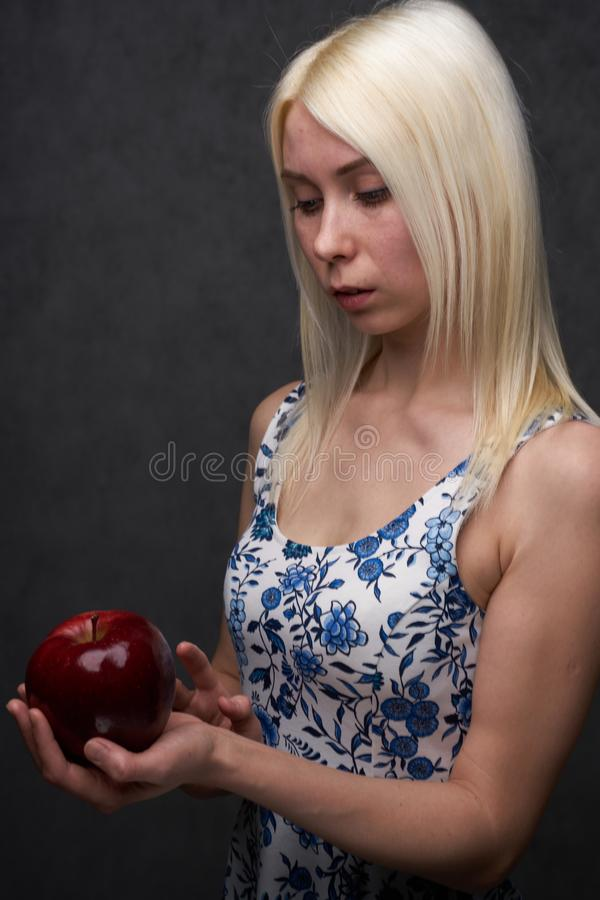 Beautiful girl in a fashionable dress with apple royalty free stock image