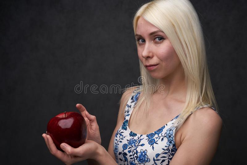 Beautiful girl in a fashionable dress with apple. Portrait composition stock image
