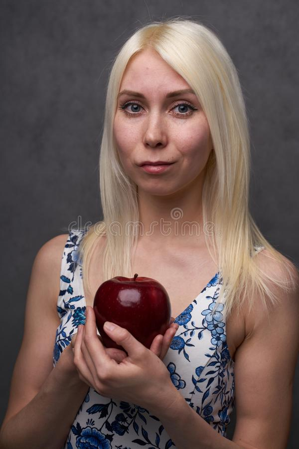 Beautiful girl in a fashionable dress with apple royalty free stock photography