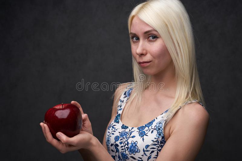 Beautiful girl in a fashionable dress with apple stock photography
