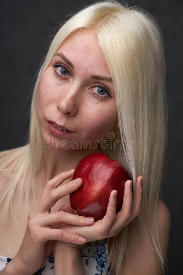 Beautiful girl in a fashionable dress with apple stock photo
