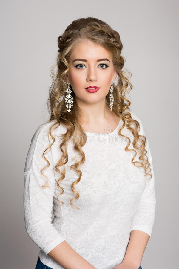 Beautiful girl with a fashionable hairdress with curls. On a gray background stock photos