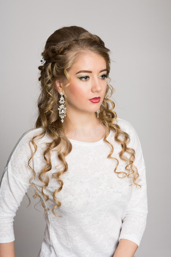 Beautiful girl with a fashionable hairdress with curls. On a gray background stock photo
