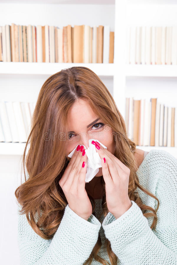 Beautiful girl feeling ill caught cold sniffles blowing her nose stock photo