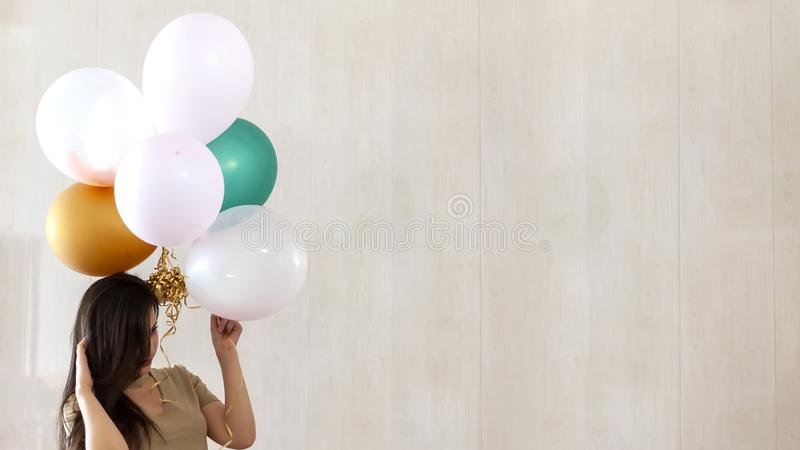 Beautiful girl with festive air balloons in hands. Young attractive female with balloons. Portrait of charming, pretty girl. Beautiful girl with festive air royalty free stock photography