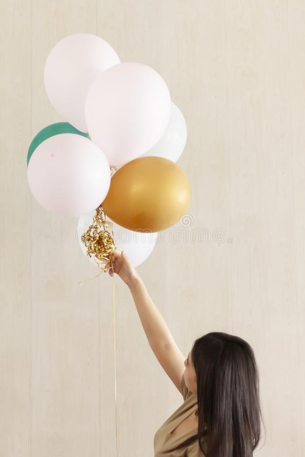 Beautiful girl with festive air balloons in hands. Young attractive female with balloons. Portrait of charming, pretty girl. Beautiful girl with festive air stock photo