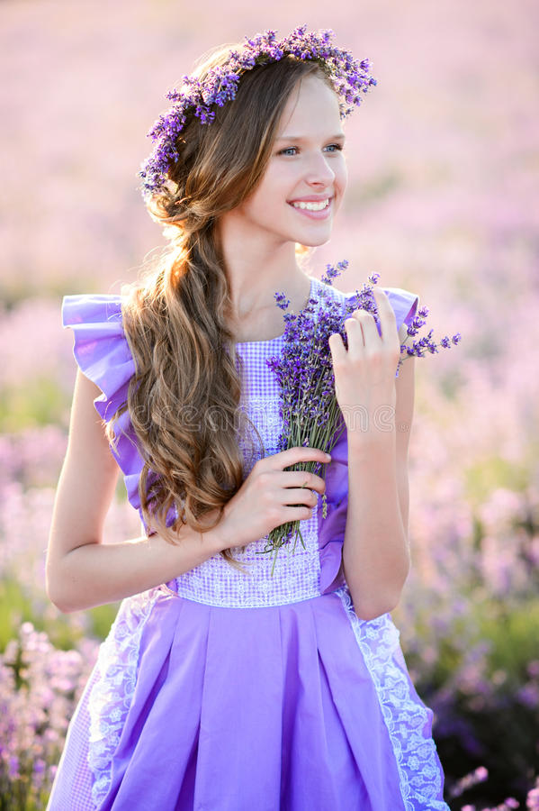 Beautiful girl in a field of lavender on sunset. stock photos