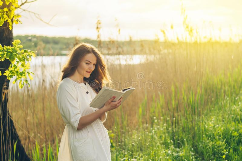 Beautiful girl in field reading a book. The girl sitting on a grass, reading a book. Rest and reading royalty free stock images