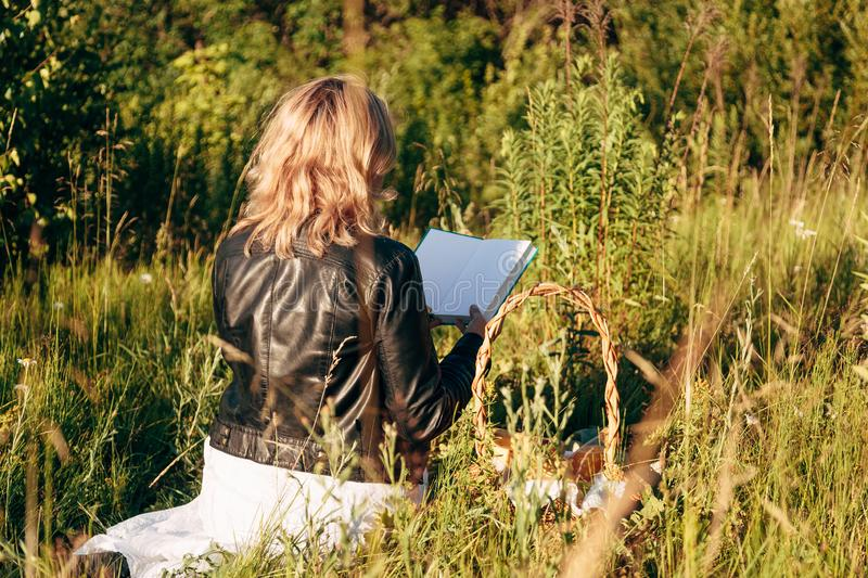 Girl in field reading a book. The girl sitting on a grass, reading a book stock photos