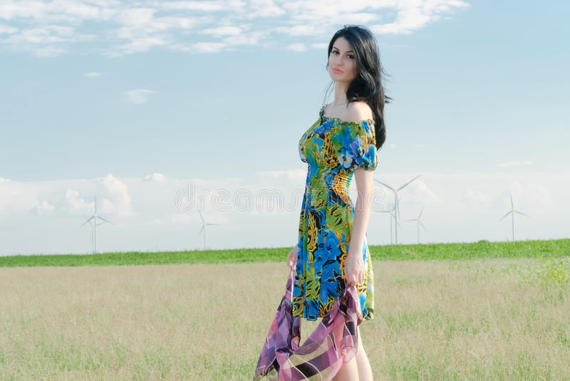Beautiful girl on the field with windmills in the background royalty free stock photography