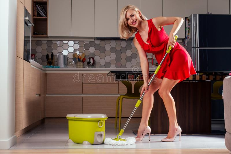 Beautiful girl floor dancing with mop and bucket in evening dress and heel shoes in a cozy apartment with a TV in the. Hall.wife is waiting for her husband at stock photos