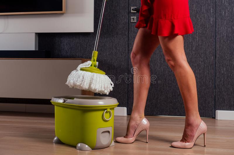 Beautiful girl floor dancing with mop and bucket in evening dress and heel shoes in a cozy apartment with a TV in the. Hall.wife is waiting for her husband at royalty free stock images