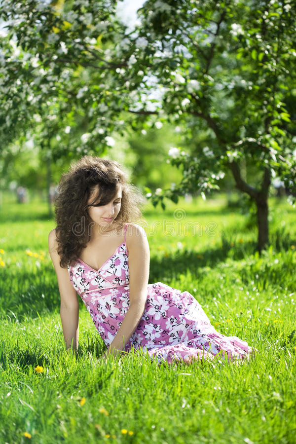Beautiful girl in the flowered garden. The image of a beautiful girl in the flowered garden stock images
