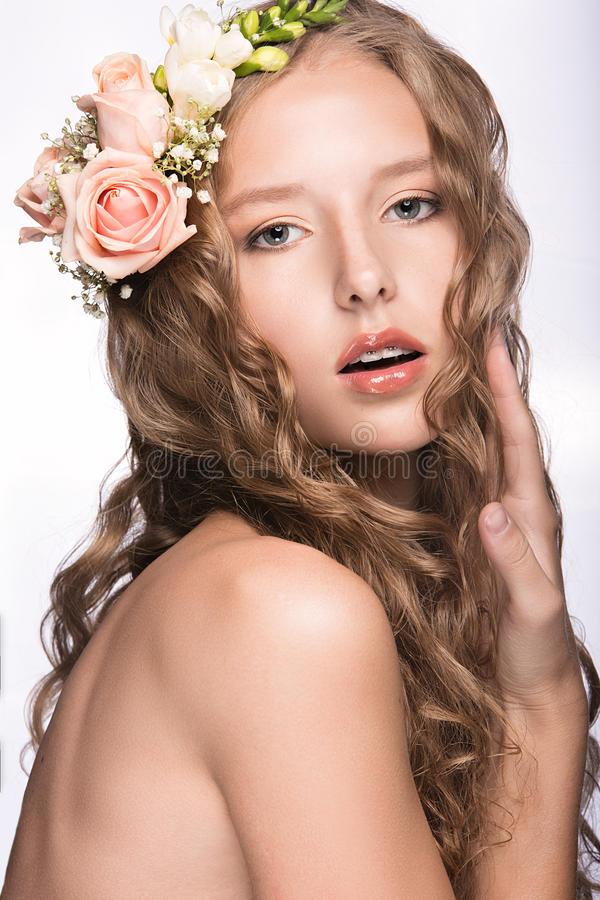 Beautiful girl with flowers in her hair and pink makeup. Spring image. Beauty face. Picture taken in the studio on a white background stock photos