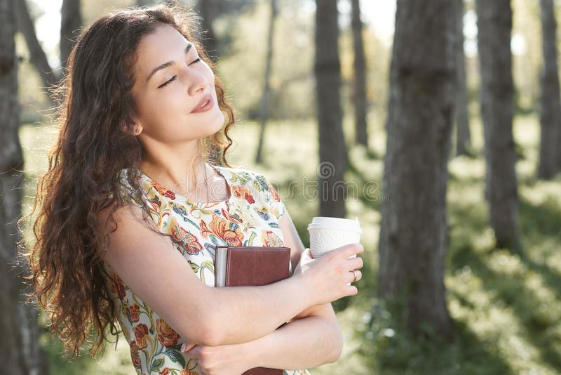 Beautiful girl in the forest, bright sunlight around, green grass and trees royalty free stock photos