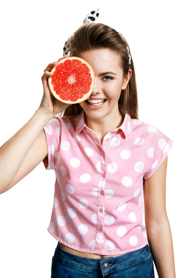Beautiful girl with fresh ripe grapefruit slice, health and beauty care concept royalty free stock images