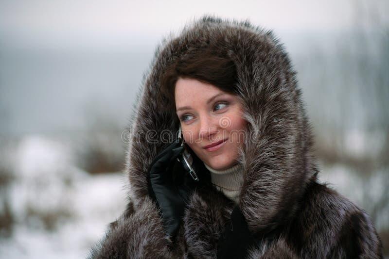 Beautiful girl in a fur coat royalty free stock photos