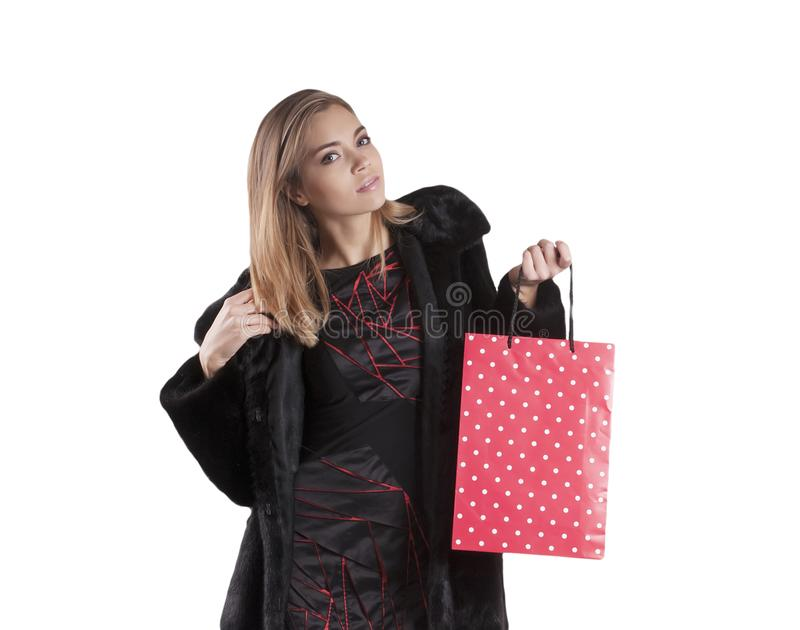 Beautiful girl in a fur coat package for shopping isolated royalty free stock photography