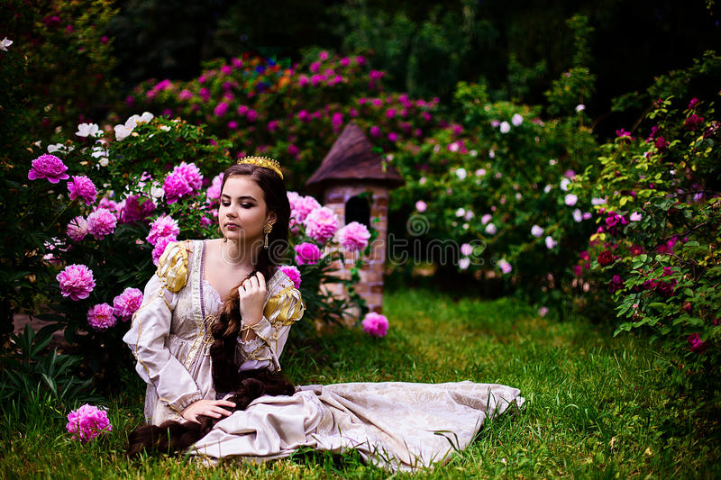 Beautiful girl in the garden with flowers in princess dress. With long braided hair stock photos