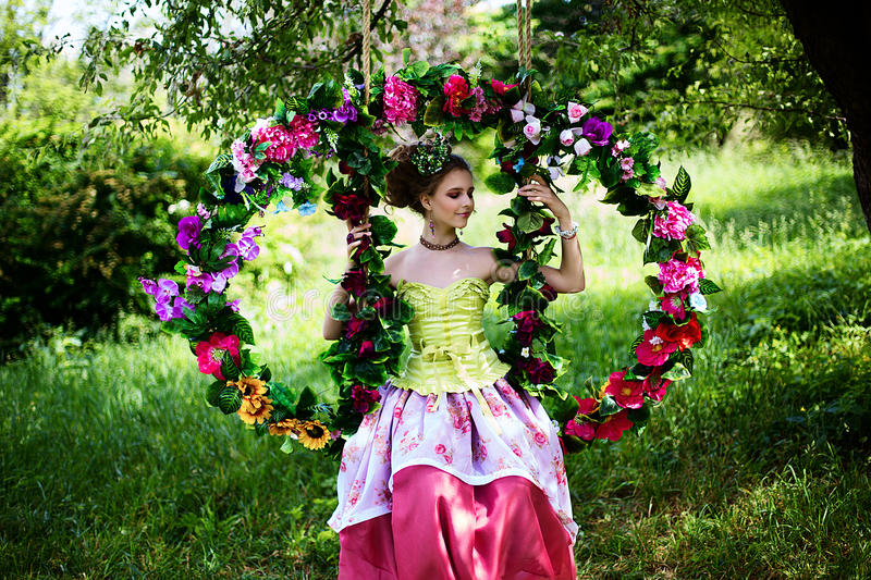 Beautiful girl in the garden with flowers in princess dress. With long braided hair stock photography