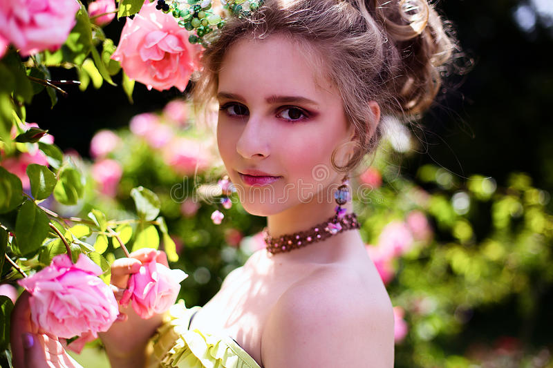 Beautiful girl in the garden with flowers in princess dress. With long braided hair royalty free stock photography