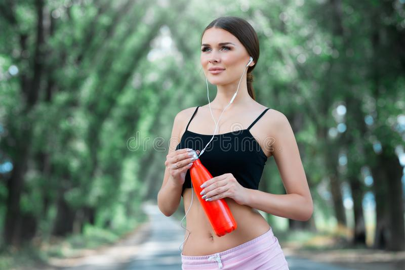 Beautiful girl getting ready for jogging in the park. With thermos bottle in hand. Part 2 stock photos