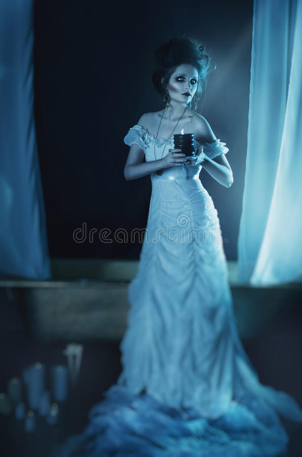 Beautiful girl ghost, witch bride in a white dress holding a black burning candle in hands stock photography