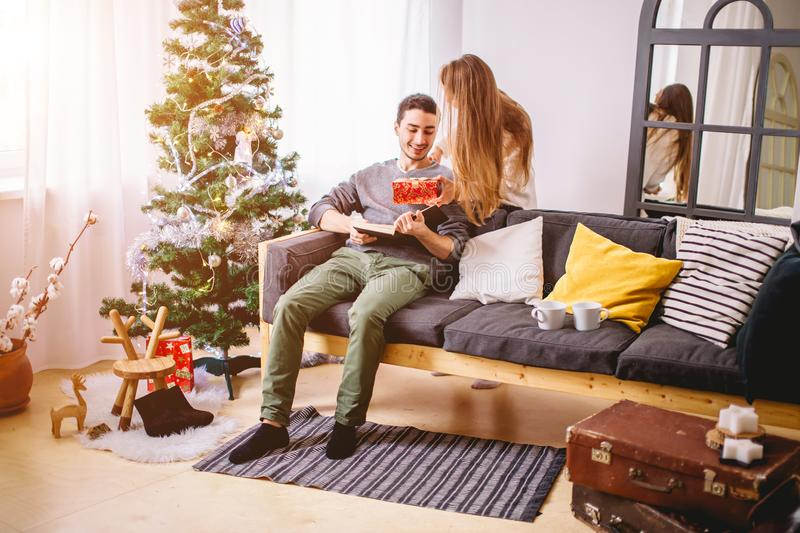 Beautiful girl gives her boyfriend a present near christmas tree royalty free stock photography