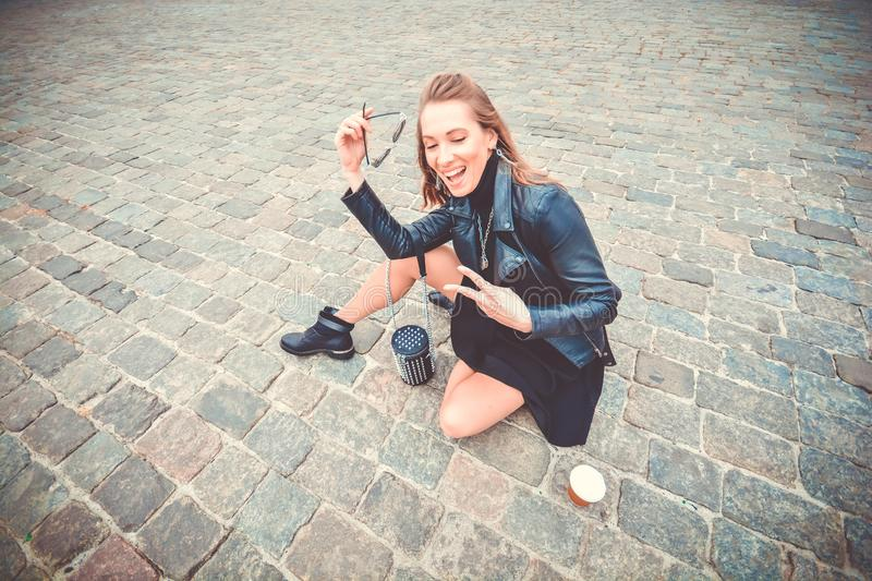 Beautiful girl in glam rock style wear sitting on a paving stones and showing peace sign.  royalty free stock photos