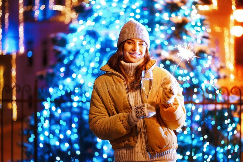 Beautiful girl with a glass of champagne and sparkle in the open air on the background of christmas tree in a winter royalty free stock photo