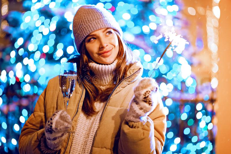 Beautiful girl with a glass of champagne and sparkle in the open air on the background of christmas tree in a winter stock photo