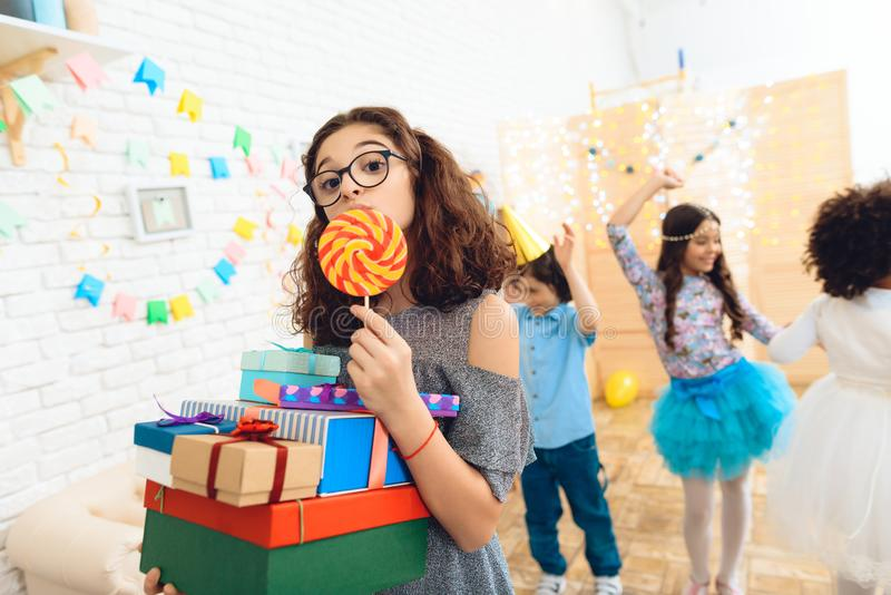Beautiful girl with glasses and bunch of gifts in hands licks colored lollipop at her birthday. Happy birthday party. Festive mood concept stock images