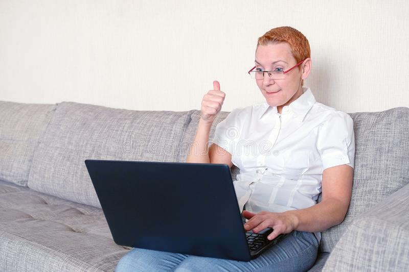 A beautiful girl in glasses with a red frame works at the laptop. Emotion of joy with the gesture of a successful transaction royalty free stock image
