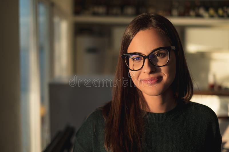 Beautiful girl with glasses smiling and standing by the window royalty free stock image
