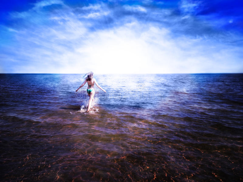 Beautiful girl going on shining water towards rising sun. Beautiful girl going on shining water of blue sea towards rising sun. She feels freedom and happiness royalty free stock photo