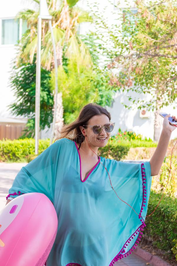 Beautiful girl is going to the beach with an inflatable circle listening to music on phone and having fun.  stock image