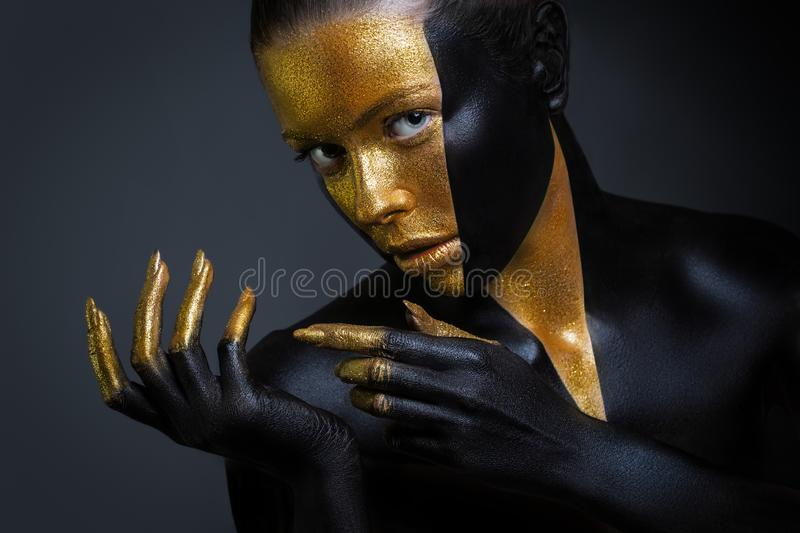 Beautiful girl with gold and black paint on her face and body. Female portrait with creative makeup stock images