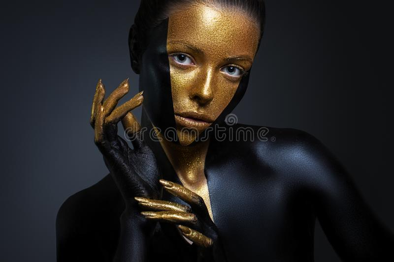 Beautiful girl with gold and black paint on her face and body. Female portrait with creative makeup. The particles of the metal powder for gold paint stock image