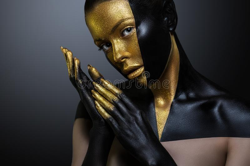 Beautiful girl with gold and black paint on her face and body. Female portrait with creative makeup. The particles of the metal royalty free stock photo