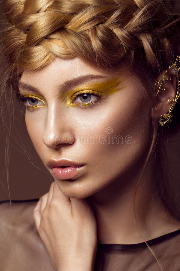 Beautiful girl in a gold dress with creative makeup and braids on her head. The beauty of the face. Photos shot in the studio royalty free stock image