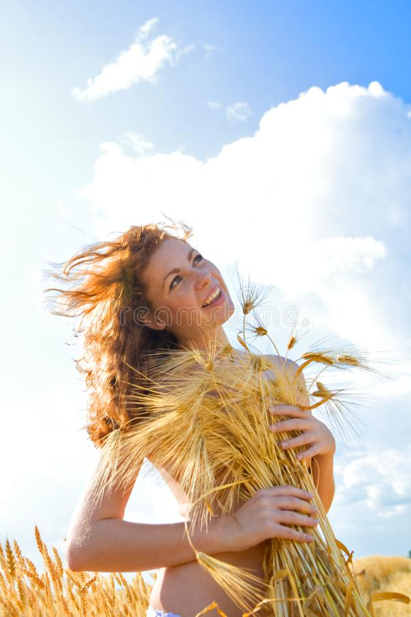 Beautiful girl on golden wheat field royalty free stock image
