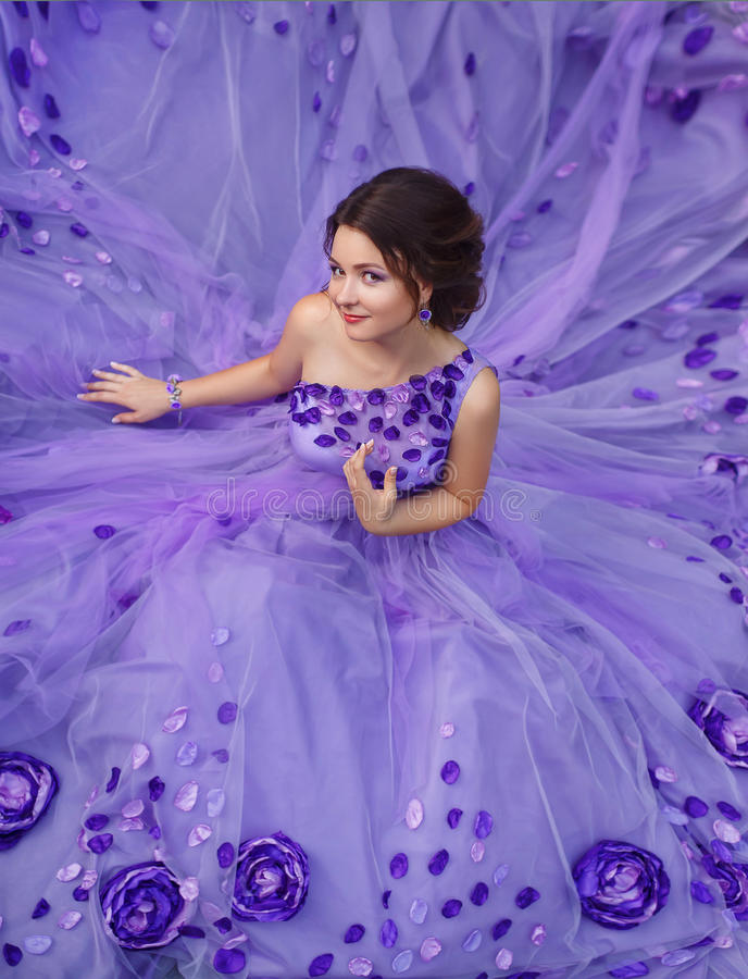 Beautiful girl in a gorgeous purple long dress. stock photography