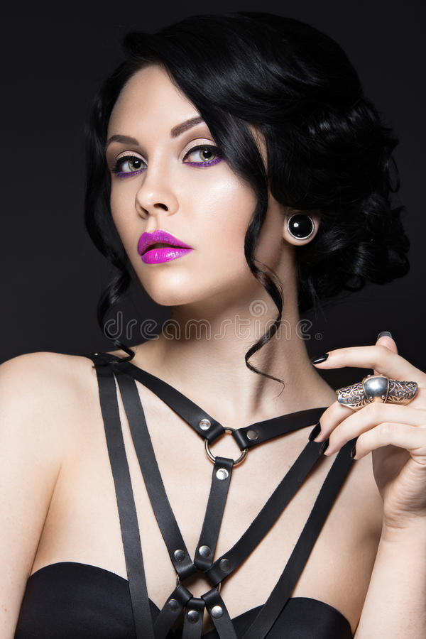 Beautiful Girl in the Gothic style with leather accessories and bright makeup. Beauty face. Picture taken in the studio on a black background stock photography