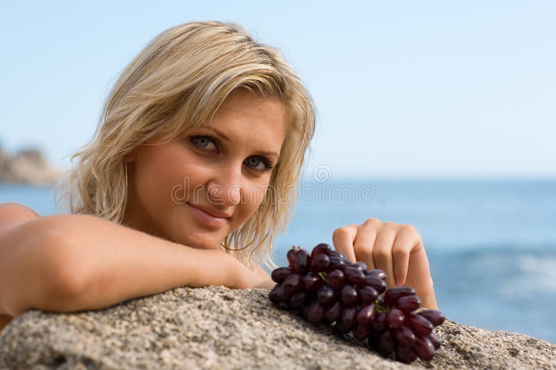 Beautiful girl and grapes. At the beach by the sea stock photos