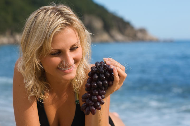 Beautiful girl with grapes. On the beach by the sea stock image