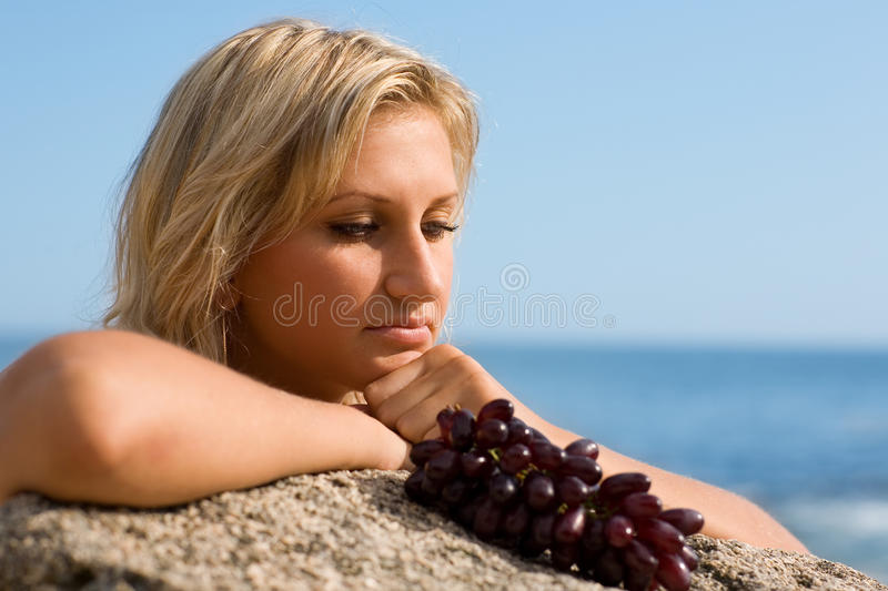 Beautiful girl and grapes. At the beach by the sea stock photography