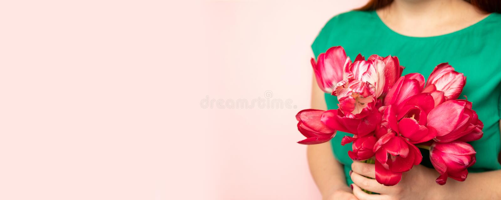 Beautiful girl in the green dress with flowers tulips in hands on pink background stock photo