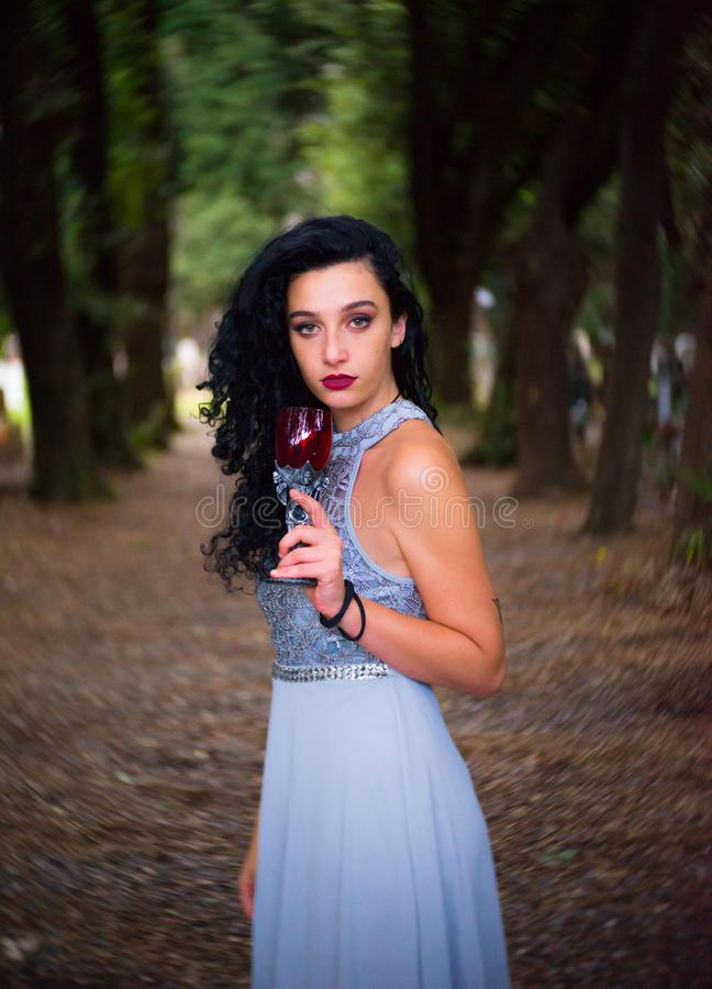 Drinking summer wine in the woods. A beautiful girl with a grey gown and black curly hair is looking at the camera with a glass of red wine. Dark bokeh in the royalty free stock photography