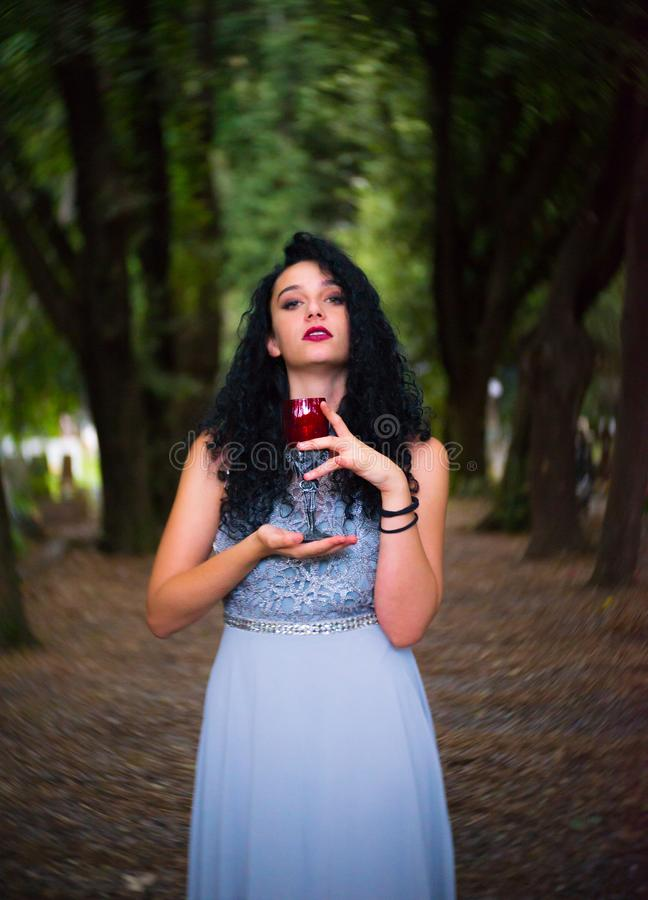 Drinking summer wine in the woods. A beautiful girl with a grey gown and black curly hair is looking at the camera with a glass of red wine. Dark bokeh in the stock photos